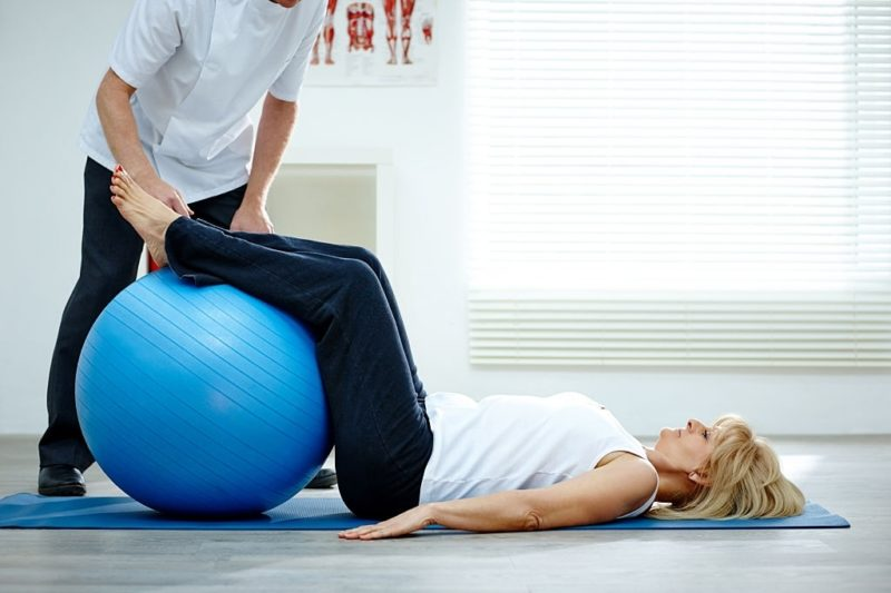 PT with legs on ball