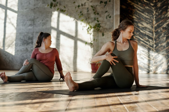 2 women doing pelvic stretches for pain